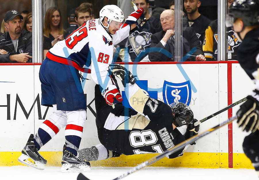 Jay Beagle #83 of the Washington Capitals hits Sidney Crosby #87 of the Pittsburgh Penguins along the boards in the third period during the game at Consol Energy Center in Pittsburgh, Pennsylvania on December 14, 2015. (Photo by Jared Wickerham / DKPS)
