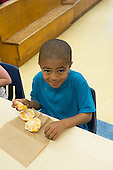 MR / Schenectady, NY. Zoller Elementary School (urban public school). Kindergarten classroom. Boy (5, African American) with fresh fruit (an orange) at snack time. MR: Ste14. ID: AM-gKw. © Ellen B. Senisi.