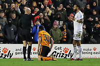 Kyle Bartley of Swansea City (R) sees a yellow card by referee Anthony Taylor (L) for his foul against Leon Bonatini of Wolverhampton Wanderers (C) during the Emirates FA Cup match between Wolverhampton Wanderers and Swansea City at The Molineux Stadium, Wolverhampton, England, UK. Saturday 06 January 2018
