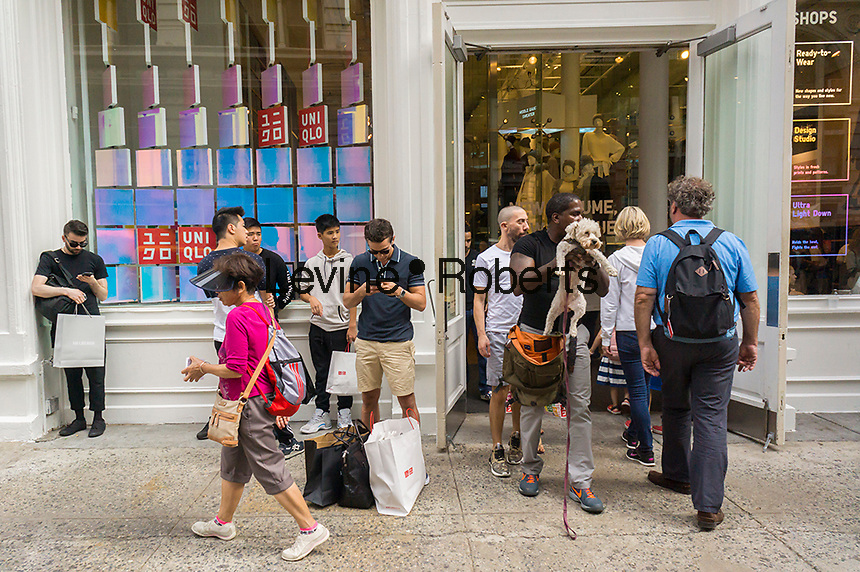 Shopping outside the newly renovated Uniqlo store in Soho in New York on Saturday, September 3, 2016. (©Richard B. Levine)