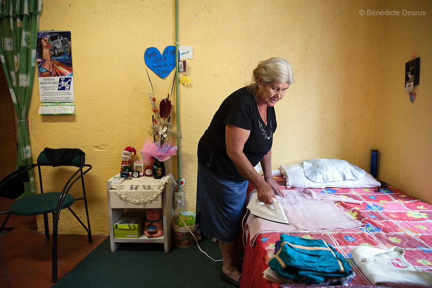 Gloria, a resident of Casa Xochiquetzal, irons her clothes in her bedroom at the shelter in Mexico City, Mexico on May 24, 2013. Casa Xochiquetzal is a shelter for elderly sex workers in Mexico City. It gives the women refuge, food, health services, a space to learn about their human rights and courses to help them rediscover their self-confidence and deal with traumatic aspects of their lives. Casa Xochiquetzal provides a space to age with dignity for a group of vulnerable women who are often invisible to society at large. It is the only such shelter existing in Latin America. Photo by Bénédicte Desrus