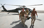 Dutch military personnel bringing in a victim of a roadside bomb on a stretcher just arrived by helicopter for hospital treatment.