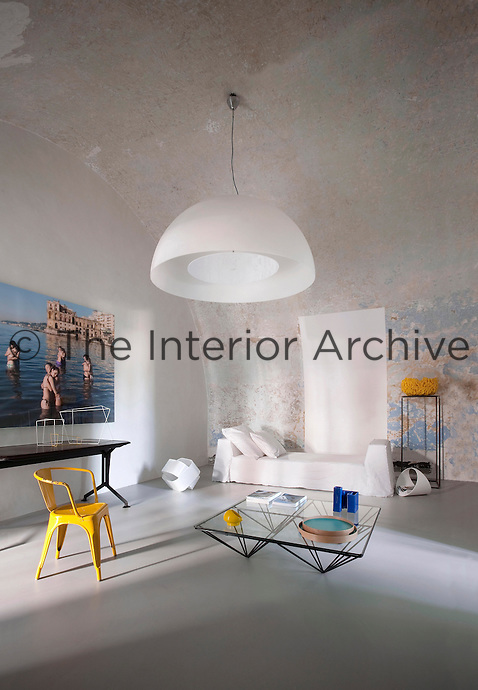 The original distressed vaulted ceiling contrasts with the contemporary furnishings and a photograph by Luciano Romano in the living room