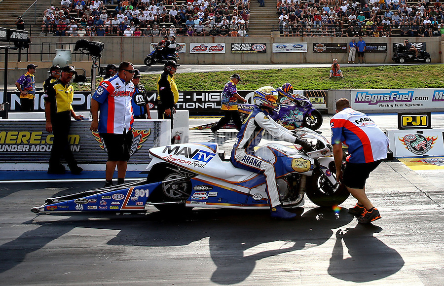 Jul. 19, 2013; Morrison, CO, USA: NHRA crew members with pro stock motorcycle rider Adam Arana during qualifying for the Mile High Nationals at Bandimere Speedway. Mandatory Credit: Mark J. Rebilas-