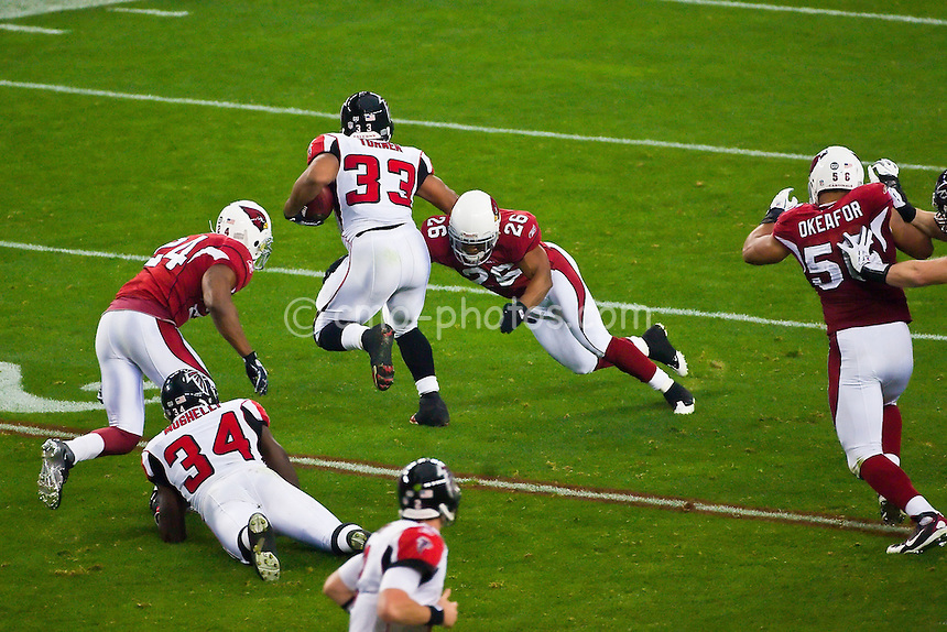 Jan 03, 2009; Glendale, AZ, USA; Arizona Cardinals cornerback Roderick Hood (26) tackles Atlanta Falcons running back Michael Turner (33) around the legs while Arizona Cardinals safety Adrian Wilson and defensive end Chike Okeafor (56) run in pursuit after shedding blocks in the first quarter of the NFC Wild Card Playoff Game at University of Phoenix Stadium.  The Cardinals won the game 30-24.