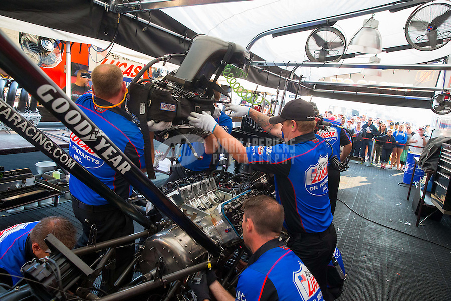 Jul 31, 2015; Sonoma, CA, USA; Crew members for NHRA top fuel driver Richie Crampton work on the engine in the pits during qualifying for the Sonoma Nationals at Sonoma Raceway. Mandatory Credit: Mark J. Rebilas-