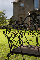 A view through the ornate ironwork of a garden bench towards Yorebridge House