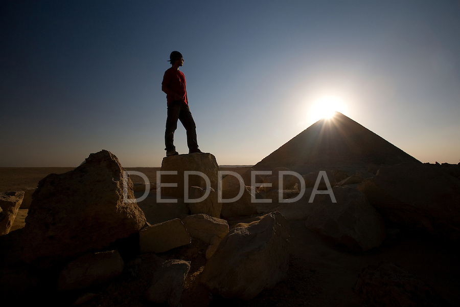 A male tourist wearing a red shirt visits the ancient site of the Red Pyramid, the world's oldest true pyramid, also known as the North Pyramid, located 10km south of Saqqara in Dahshur, Egypt.