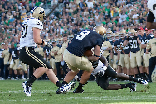 Notre Dame tight end Kyle Rudolph (#9) is tackled by Purdue cornerback Charlton Williams (#15) in game action during NCAA football game between the Notre Dame Fighting Irish and the Purdue Boilermakers.  Notre Dame defeated Purdue 23-12 in game at Notre Dame Stadium in South Bend, Indiana.
