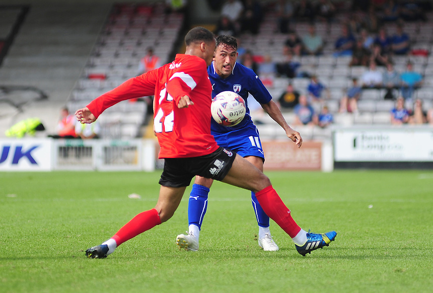 Chesterfield's Gary Roberts plays the ball past Lincoln City's Jake Caprice<br /> <br /> Photographer Chris Vaughan/CameraSport<br /> <br /> Football - Friendly - Lincoln City v Chesterfield - Saturday 19th July 2014 - Sincil Bank Stadium - Lincoln<br /> <br /> &copy; CameraSport - 43 Linden Ave. Countesthorpe. Leicester. England. LE8 5PG - Tel: +44 (0) 116 277 4147 - admin@camerasport.com - www.camerasport.com