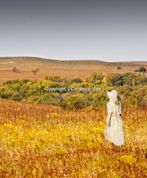 A woman wearing a long white dress walks through the golden field of the Kansas Flint Hills.