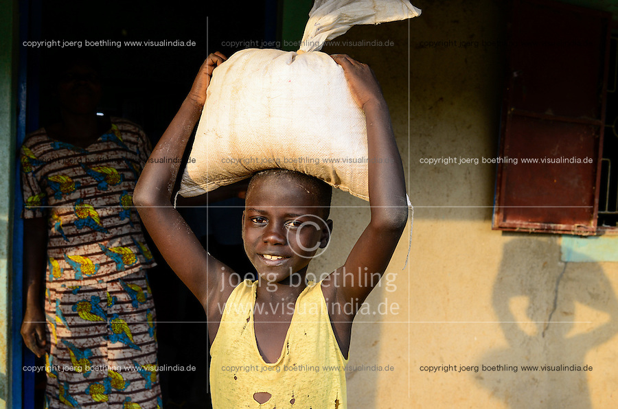 KENYA, County Siaya, village Kotanega, boy with maize flour bag infront of posho mill / KENIA, kleine Maismuehle, Junge mit Mehlsack