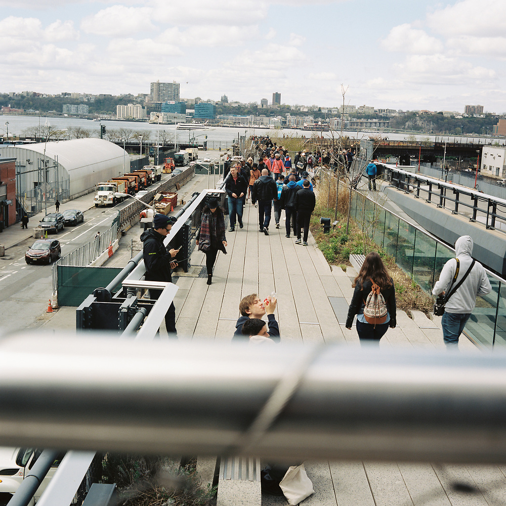 People walk the High Line near the intersection of 11th Avenue and West 30th Street in Manhattan, New York on Sunday, April 29, 2018. (Photo by James Brosher)