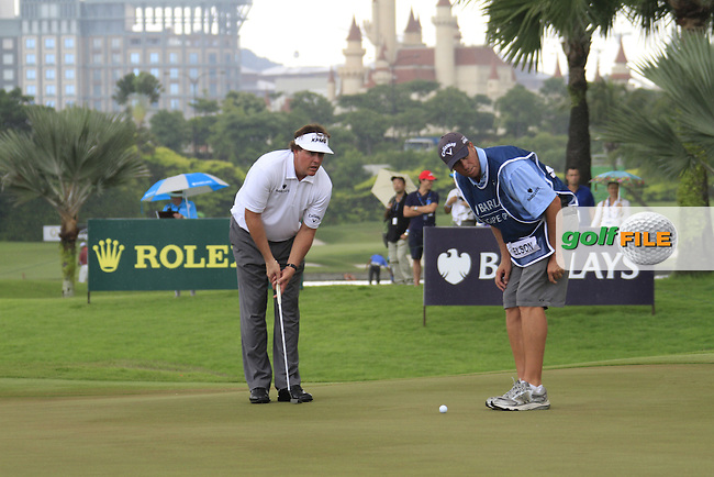 Phil Mickelson (USA) and caddy Jim Makay line up his putt on the 12th green during the rain delayed Round 3 of the 2011 Barclays Singapore Open, Singapore, 12th November 2011 (Photo Eoin Clarke/www.golffile.ie)