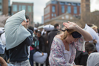 NEW YORK CITY, NY - APRIL 2 : A woman covers herself of being hit by pillows while people take part during the International pillow fight event in Washington Square Park on April 2, 2016 in New York City, New York. Thousands of people of all ages attend the free global event in different cities worldwide celebrating the 11th annual International Pillow Fight in New York. Photo by VIEWpress/Maite H. Mateo
