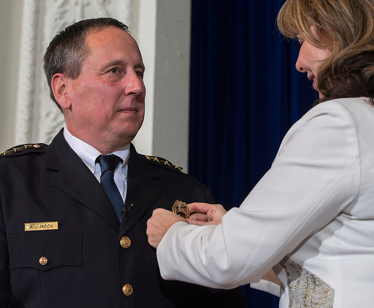 Charlene Mock, right, pins the badge on Houston ISD Chief of Police Robert Mock, left, during a ceremony, January 6, 2014, at the High School for Law Enforcement and Criminal Justice.
