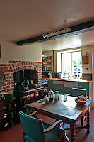 The cosy kitchen is warmed by the range with plenty of room for a gate-legged table and two armchairs in front