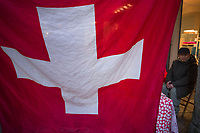 Switzerland. Canton Ticino. Lugano. City center. A giant swiss flag and a seated a Chinese man. Street vendor selling Chinese food. The flag of Switzerland (German: Schweizerfahne; French: drapeau de la Suisse; Italian: bandiera svizzera; Romansh: bandiera de la Svizra) displays a white cross in the centre of a square red field. The white cross is known as the Swiss cross. 1.01.2020  © 2020 Didier Ruef