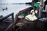 LUKUTU, DEMOCRATIC REPUBLIC OF CONGO MARCH 15: Clarisse Mondo, age 13, waits for a boat to leave on March 15, 2006 in Lukutu, Congo, DRC. Clarisse traveled from Kisangani by herself as her sister died and she?s now going to look for her mother in Bumba, a journey of about a week. She haven?t seen her for ten years and don?t know her address. About five hundred people traveled on the boat from Kisangani to Kinshasa, a journey of about 1750 kilometers. It takes from 3-7 weeks, depending on the boat. Congo River is a lifeline for millions of people, who depend on it for transport and trade. During the Mobuto era, big boats run by the state company ONATRA dominated the traffic on the river. These boats had cabins and restaurants etc. All the boats are now private and are mainly barges that transport goods. The crews sell tickets to passengers who travel in very bad conditions, mixing passengers with animals, goods and only about two toilets for five hundred passengers. The conditions on the boats often resemble conditions in a refugee camp. Congo is planning to hold general elections by July 2006, the first democratic elections in forty years. (Photo by Per-Anders Pettersson)