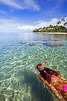 A girl/woman snorkels in clear water at Lahaina, Maui.