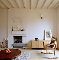 The living room has a brick floor and is furnished with retro wooden furniture