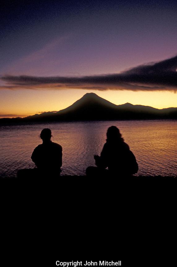 Young tourists, watchong the sun set over Lake Atitlan, Guatemala, at dusk