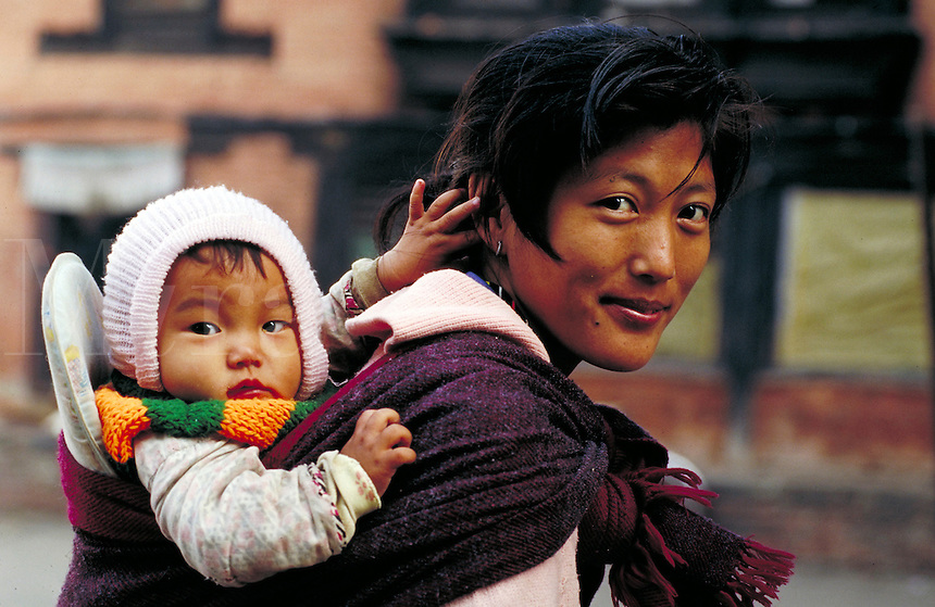 Tibetan mother with papoose smiles; head and shoulders from right side; both look toward camera. Kathmandu, Nepal.