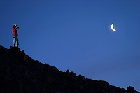 Man standing below crescent moon on silhouetted ridge line under a clear night sky, Lower Saddle, Grand Teton National Park, Teton County, Wyoming, USA