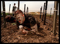 ME.Mud.Crawl .0314.KC--Tustin Marine Corps Air Station--With drink in hand Sargeant Steve Rhoads makes his way through the low crawl pit part of the 6.2 mile course for the 15th annual Volkslauf Mud Run..Mandatory Credit: Kevin P. Casey/The LA Times