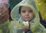 A refugee child eats an apple as she approaches the border into Croatia near the Serbian village of Berkasovo. Hundreds of thousands of refugees and migrants from Syria, Iraq and other countries--including many children--have flowed through Serbia in 2015, on their way to western Europe.