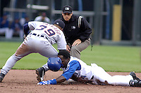 Second base umpire Mark Wegner looks intently at Detroit Tigers second baseman Ramon Santiago's tag on Royals shortstop Angel Berroa as he slides into second on a double to left-center at Kauffman Stadium in Kansas City, Missouri on April 20, 2003. The Royals won 4-3.