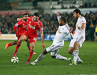 SWANSEA, WALES - MARCH 16: Joe Allen of Liverpool (L) avoids a tackle by former team mate Ashley Williams of Swansea (C)during the Premier League match between Swansea City and Liverpool at the Liberty Stadium on March 16, 2015 in Swansea, Wales