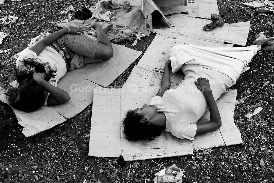 Nicaraguan girls, addicted to the glue sniffing, sleep on the cardboard in the park, Managua, Nicaragua, 5 November 2004. Hundreds of kids struggle on the streets of Managua, sniffing glue to avoid hunger and get out of the misery. The glue is the cheapest drug available in every slum in Latin America. It is widely sold to the kids because there is no government control, neither restriction. The police can not intervene because the glue is not legally considered as a drug. Many sniffers end up with permanent brain damage, their motion ability is reduced, some of them keep in unstoppable tremor till the end of the life.