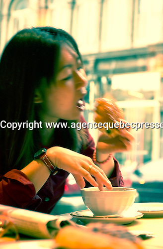 June 16 , 2002, Montreal, Quebec, Canada<br /> <br /> A Japanese tourist enjoy the French culture of Montreal<br /> by eating  a chocololate croissant and caffe latte (coffee with milk) in a Old Montreal  coffee  shop, June 16 , 2002.<br /> <br /> Model released for editorial use only.<br /> Any commercial / advertising use is subject to the coffee shop owner approval<br /> <br /> Mandatory Credit: Photo by Pierre Roussel- Images Distribution. (©) Copyright 2002 by Pierre Roussel <br /> <br /> NOTE Nikon D-1 jpeg opened with Qimage icc profile, saved in Adobe 1998 RGB. <br /> PhotoShop Cross Process Effect<br /> Original size - uncropped TIFF file available on request.