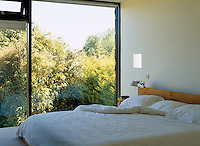 This simple bedroom has views through floor-to-ceiling windows to the garden beyond