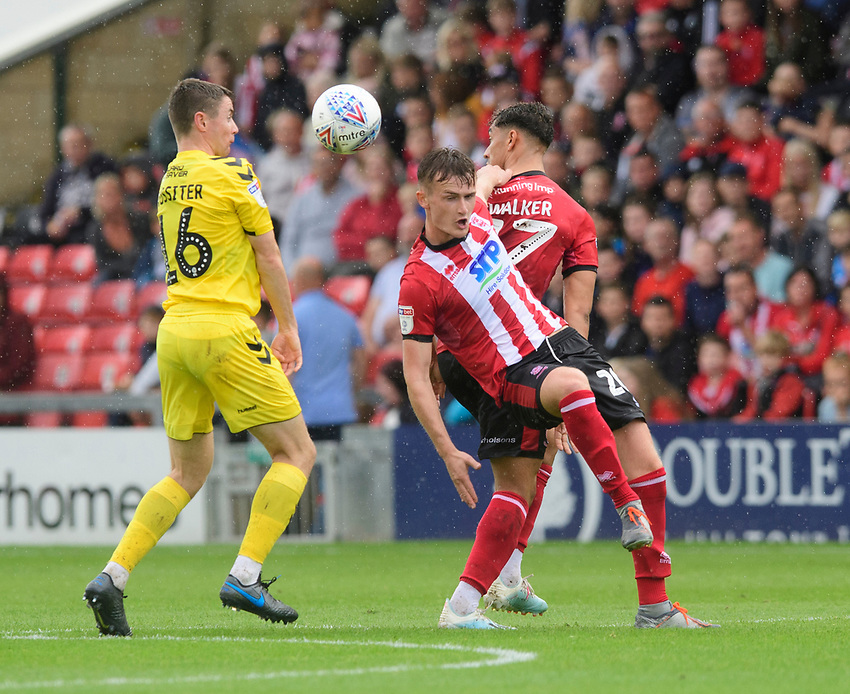 Lincoln City's Callum Connolly, centre, and Lincoln City's Tyler Walker vies for possession with Fleetwood Town's Jordan Rossiter<br /> <br /> Photographer Chris Vaughan/CameraSport<br /> <br /> The EFL Sky Bet League One - Lincoln City v Fleetwood Town - Saturday 31st August 2019 - Sincil Bank - Lincoln<br /> <br /> World Copyright © 2019 CameraSport. All rights reserved. 43 Linden Ave. Countesthorpe. Leicester. England. LE8 5PG - Tel: +44 (0) 116 277 4147 - admin@camerasport.com - www.camerasport.com