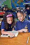 One African American female student reads book as one black mixed 7 year old girl with curly hairholds the book for her on the desk in the classroom