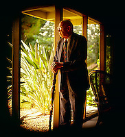 Picture of Peter Drucker taken at his home in California standing with his cane looking out the window
