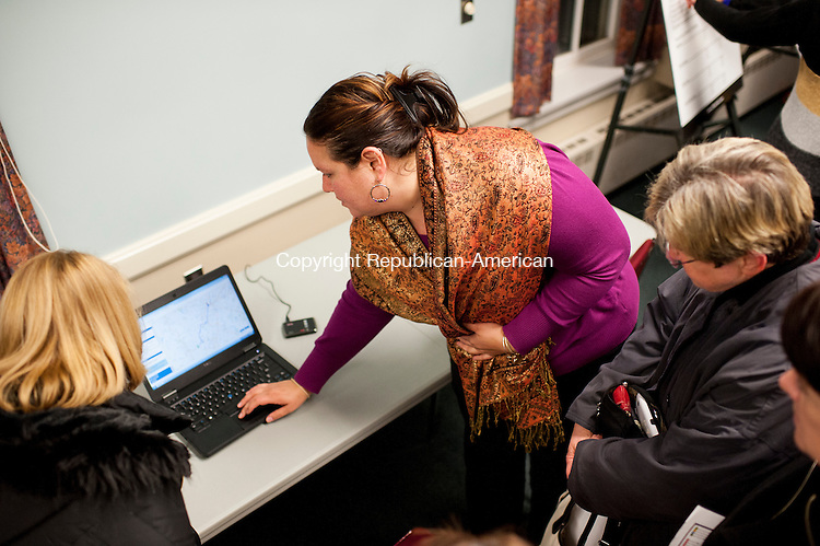 CHESHIRE, CT-21 January 2015-012115EC01-  Lizette Cruz, the Assistant Planner for CTtransit, shows residents how the CTfastrak website works. Laptops and maps were placed throughout Cheshire Town Hall Wednesday night to show residents what the new rapid transit system offers. Erin Covey Republican-American