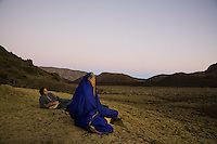 Asian-American woman wrapped in a sleeping bag, meditating in Haleakala crater with a young Caucasian man lying down next to her