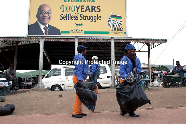 NKANDLA, SOUTH AFRICA - OCTOBER 10: Street cleaners work in front of a big billboard celebrating 100 years of selfless struggle on the main road in South African president Jacob Zuma's birth village on October 10, 2012 in KwaNxamalala, Nkandla. South Africa. The South African government is spending R240-million (about US$ 27 million) to construct the vast property for his large family. (Photo by Per-Anders Pettersson)