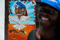 Haitian man stands in front of a mural painting in the street of Cité Soleil, Port-au-Prince, Haiti, 13 July 2008. Cité Soleil is considered one of the worst slums in the Americas, most of its 300.000 residents live in extreme poverty. Children and single mothers predominate in the population. Social and living conditions in the slum are a human tragedy. There is no running water, no sewers and no electricity. Public services virtually do not exist - there are no stores, no hospitals or schools, no urban infrastructure. In spite of this fact, a rent must be payed even in all shacks made from rusty metal sheets. Infectious diseases are widely spread as garbage disposal does not exist in Cité Soleil. Violence is common, armed gangs operate throughout the slum.