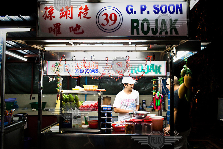 A stall owner prepares Rojak, a savoury fruit and salad dish, at a Chinese Hawker stall.