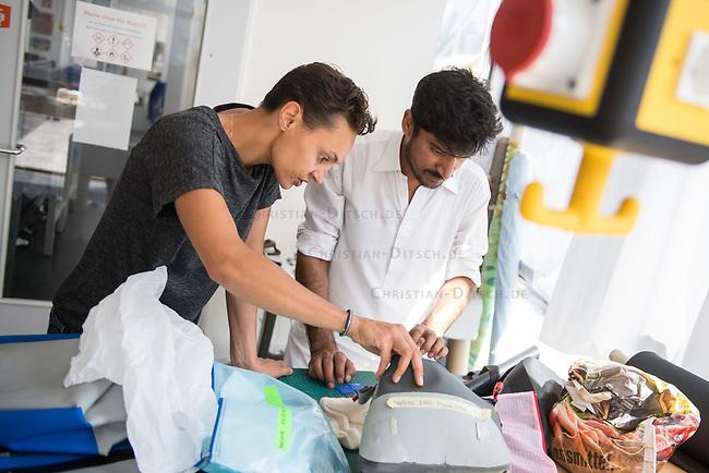 Das Berliner Start-up &quot;mimycri&quot; produziert Taschen aus den Gummiplanen gestrandeter Fluechtlingsboote.<br /> Statt Griechenlands Straende im Muell der gestrandeten Fluechtlingsboote ersticken zu lassen, stellt das Berliner Unternehmen &quot;mimycri&quot; daraus Taschen und Rucksaecke her und bietet Fluechtlingen eine Chance auf Normalitaet und Regelmaessigkeit.<br /> Im Bild vlnr.: Nora Azzaoui, 30-Jaehrige Unternehmensberaterin aus Berlin und Abid Ali, gefluechteter Schneider aus Pakistan besprechen die Nadelstaerke fuer die Naehte einer Tasche.<br /> 8.8.2017, Berlin<br /> Copyright: Christian-Ditsch.de<br /> [Inhaltsveraendernde Manipulation des Fotos nur nach ausdruecklicher Genehmigung des Fotografen. Vereinbarungen ueber Abtretung von Persoenlichkeitsrechten/Model Release der abgebildeten Person/Personen liegen nicht vor. NO MODEL RELEASE! Nur fuer Redaktionelle Zwecke. Don't publish without copyright Christian-Ditsch.de, Veroeffentlichung nur mit Fotografennennung, sowie gegen Honorar, MwSt. und Beleg. Konto: I N G - D i B a, IBAN DE58500105175400192269, BIC INGDDEFFXXX, Kontakt: post@christian-ditsch.de<br /> Bei der Bearbeitung der Dateiinformationen darf die Urheberkennzeichnung in den EXIF- und  IPTC-Daten nicht entfernt werden, diese sind in digitalen Medien nach &sect;95c UrhG rechtlich geschuetzt. Der Urhebervermerk wird gemaess &sect;13 UrhG verlangt.]
