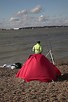 Man with red tent fishing on beach on River Orwell next to Port of Felixstowe . Concept of industry co-existing with leisure and the environment.