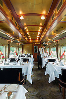 Travelling in style on the Eastern & Oriental Express from Bangkok to Singapore. A steward preparing for lunch in one of the two dining cars.