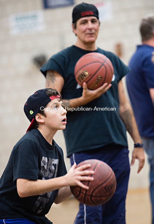 """WOODBURY, CT - 20 November 2015-112015EC17--  Joey DeLucia, 12, a student at Woodbury Middle School, tries to sink a free-throw to win Thanksgiving dinner during a """"Turkey Shoot"""" at the school Friday night. His father, Marty DeLucia, also took part in the event. Depending on how many baskets they made, contestants brought home turkey, pies, stuffing and cranberry sauce. Erin Covey Republican-American."""