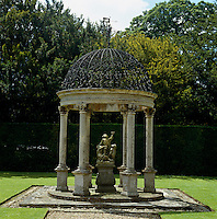 A gazebo with an ornate wrought-iron domed roof has a stone sculpture at its centre