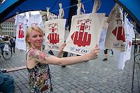 """Bilderberg-Treffen in Dresden.<br /> Verschiedene Rechte, Nazis, Pegida-Teilnehmer und Anhaenger von Verschwoerungstheorien protestierten am Samstag den 11. Juni 2016 in Dresden gegen ein Treffen der sog. """"Bilderberger"""" im Taschenberg Palais. Bei diesem Treffen, das seit 1954 stattfindet, versammeln sich Regierungenangehoerige, Mitglieder wichtiger Think-Tanks und Industrielle verschiedener westlicher Staaten zu einem geheimen Treffen um sich auszutauschen. Ergebnisse dieser Treffen werden nicht veroeffentlicht.<br /> Im Bild: Eine Demonstrantin haengt Stofftaschen mit Aufdruck gegen das Freihandelsabkommen TTIP auf.<br /> 11.6.2016, Dresden<br /> Copyright: Christian-Ditsch.de<br /> [Inhaltsveraendernde Manipulation des Fotos nur nach ausdruecklicher Genehmigung des Fotografen. Vereinbarungen ueber Abtretung von Persoenlichkeitsrechten/Model Release der abgebildeten Person/Personen liegen nicht vor. NO MODEL RELEASE! Nur fuer Redaktionelle Zwecke. Don't publish without copyright Christian-Ditsch.de, Veroeffentlichung nur mit Fotografennennung, sowie gegen Honorar, MwSt. und Beleg. Konto: I N G - D i B a, IBAN DE58500105175400192269, BIC INGDDEFFXXX, Kontakt: post@christian-ditsch.de<br /> Bei der Bearbeitung der Dateiinformationen darf die Urheberkennzeichnung in den EXIF- und  IPTC-Daten nicht entfernt werden, diese sind in digitalen Medien nach §95c UrhG rechtlich geschuetzt. Der Urhebervermerk wird gemaess §13 UrhG verlangt.]"""