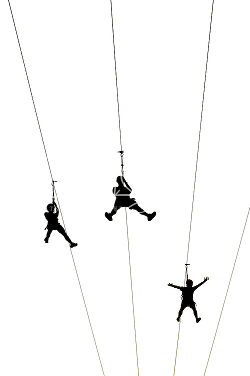 Participants take flight, zooming through the air over the US National Whitewater Center (USNWC) on the USNWC's zip-lines, part of the facilities high-adventure offerings. The popular outdoor adventure activity lets outdoor enthusiasts be secured into a harness then propelled by gravity along an inclined steel cable. Charlotte, North Carolina's US National Whitewater Center offers multiple zip lines, which vary in height and distance traveled, as well as one of the largest outdoor climbing facilities in the world. The USNWC is a non-profit outdoor recreation facility open to the public for whitewater rafting, kayaking, canoeing, rappelling, zip lining, mountain biking, hiking, climbing and more. The center opened to the public in 2006.